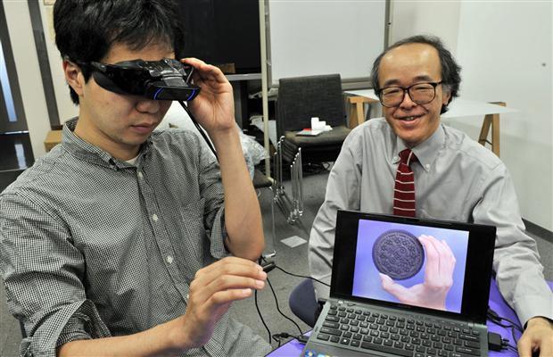 Giáo sư Michitaka Hirose bên cạnh sản phẩm kính mắt đánh lừa