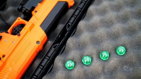 Khẩu súng lục và những viên đạn nhỏ, màu xanh chứa các mã ADN